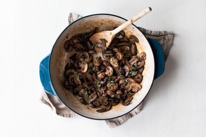 Sauteed mushrooms with garlic, butter, and thyme in a blue ceramic skillet.