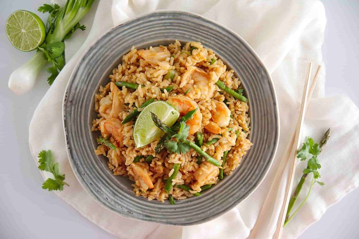 Shrimp fried rice with asparagus, cilantro, and a lime wedge in a bowl.