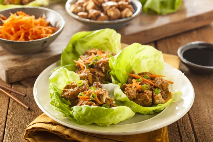Slow Cooker Korean Chicken in lettuce wraps with shredded carrots on top.
