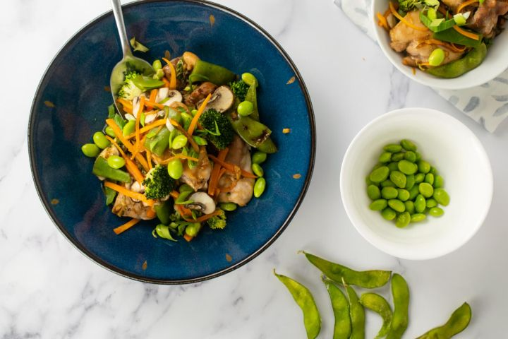 Soy chicken with vegetables including edamame, broccoli, carrots, and onions in a dish.