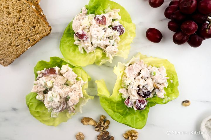 Waldorf chicken salad wrapped in lettuce with grapes, walnuts, and whole wheat bread.