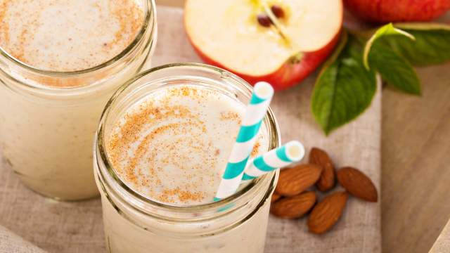 Apple Pie Smoothie in a mason jar with apples and almonds.
