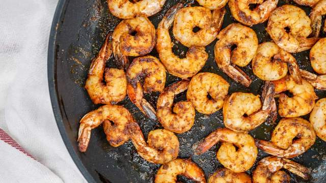 Blackened shrimp with homemade seasoning in a black skillet with butter.